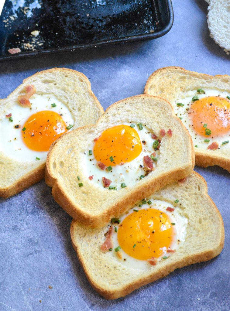 a stack of several slices of sheet pan egg in a hole bread on a gray background