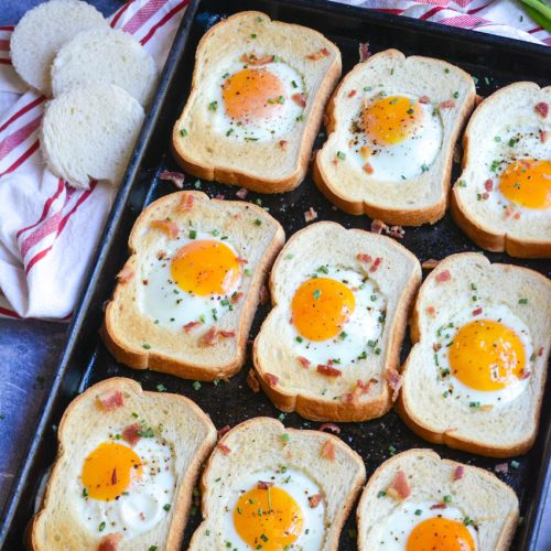 sheet pan egg in a hole shown on a dark brown sheet pan with a cloth napkin, cut out bread holes, and a bunch of green onions in the background