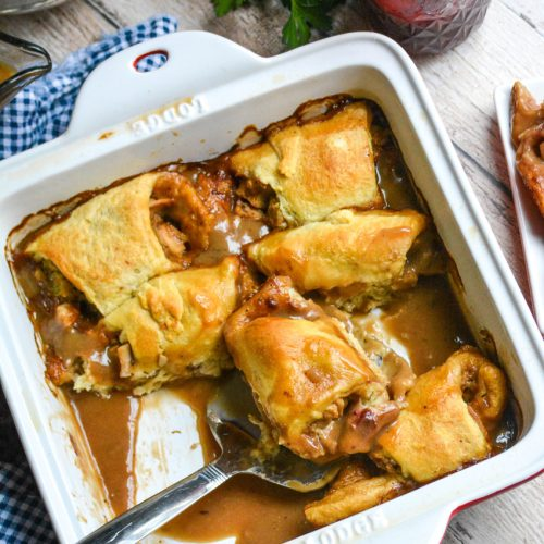 """thanksgiving leftover crescent rolls baked in gravy and shown in an 8x8"""" ceramic baking dish with a silver spatula"""