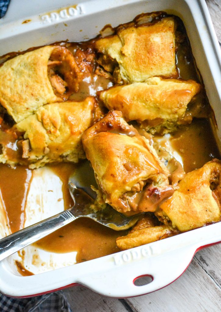 "thanksgiving leftover crescent rolls baked in gravy and shown in an 8x8"" ceramic baking dish with a silver spatula"