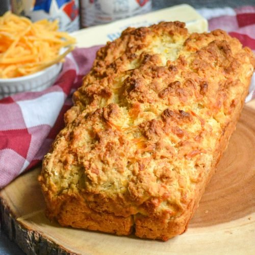 a loaf of cheesy beer bread shown on a wooden cutting board
