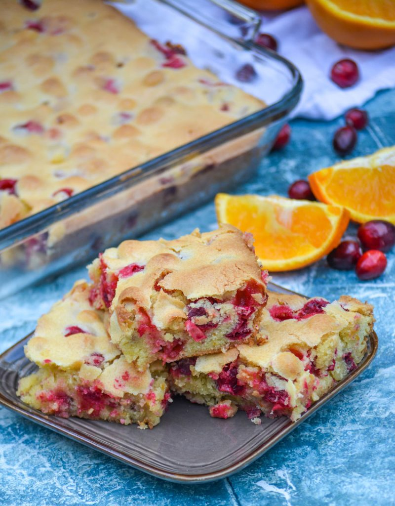 three square slices of cranberry christmas cake stacked together on top of a brown plate