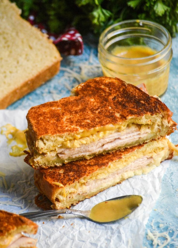 two halves of a crispy Dijon turkey melt sandwich stacked on top of each other to reveal layers of meat and melted cheese