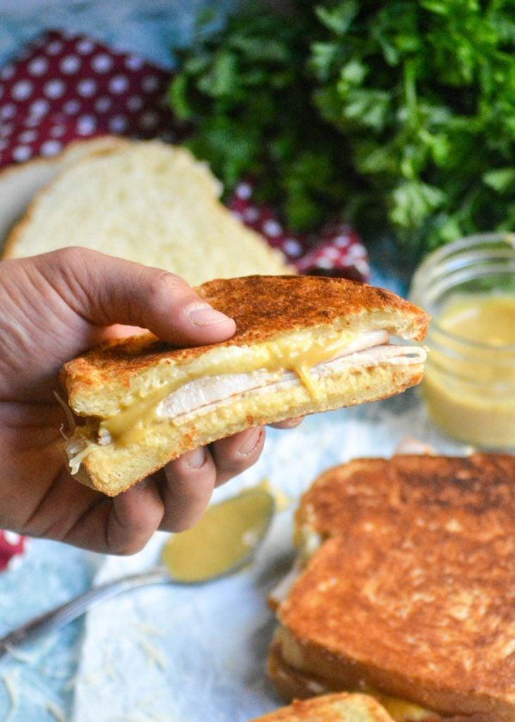 a hand holding aloft half a crispy Dijon turkey melt sandwich