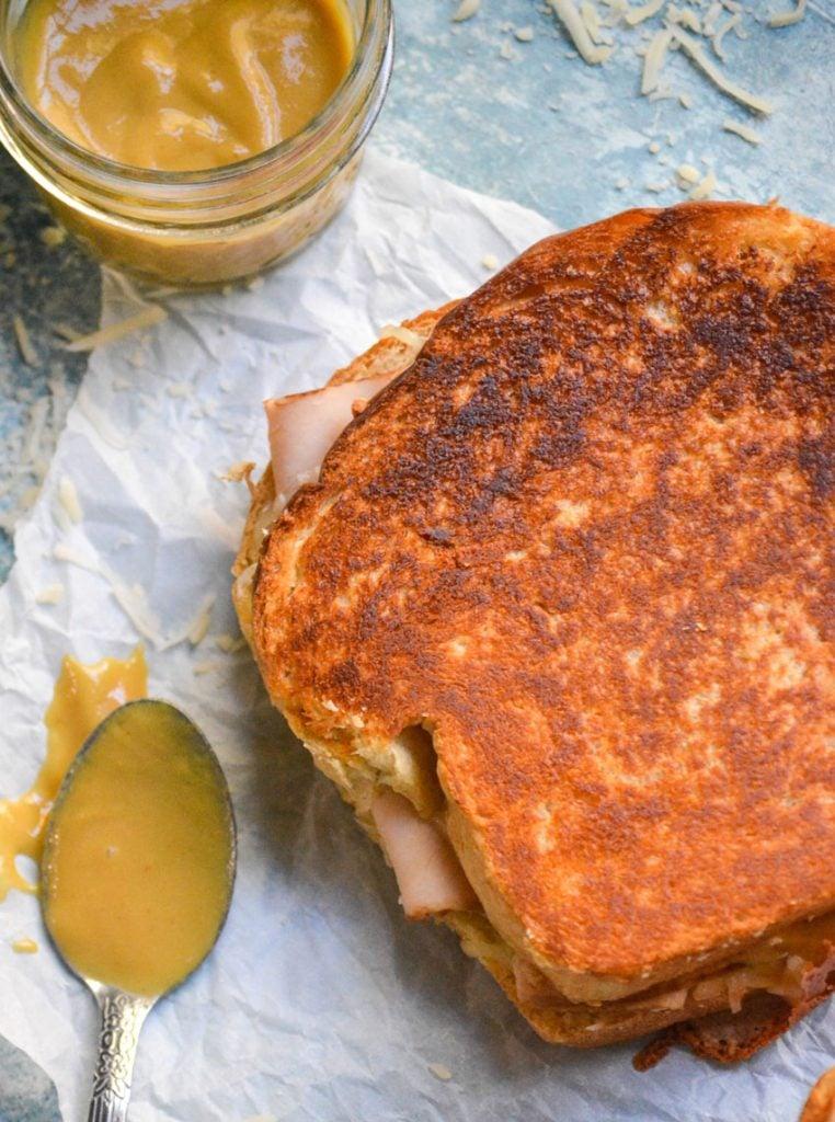a crispy Dijon turkey melt sandwich shown on parchment paper with honey Dijon mustard on a metal spoon