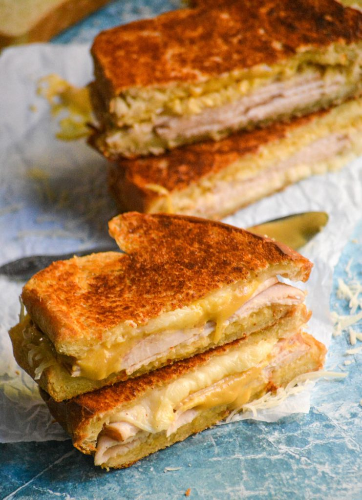 turkey Dijon melts cut in half to reveal the center, stacked, and shown on white parchment paper
