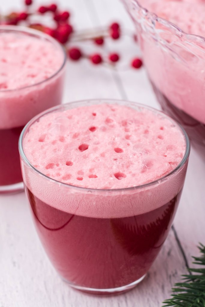 glasses filled with bright red santa snowball punch with a scoop of vanilla ice cream floating in each