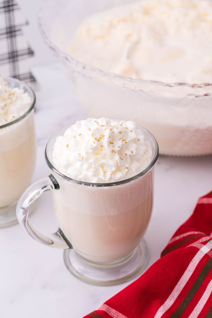 creamy white christmas punch shown in a glass jar, topped with whipped cream and golden sprinkles