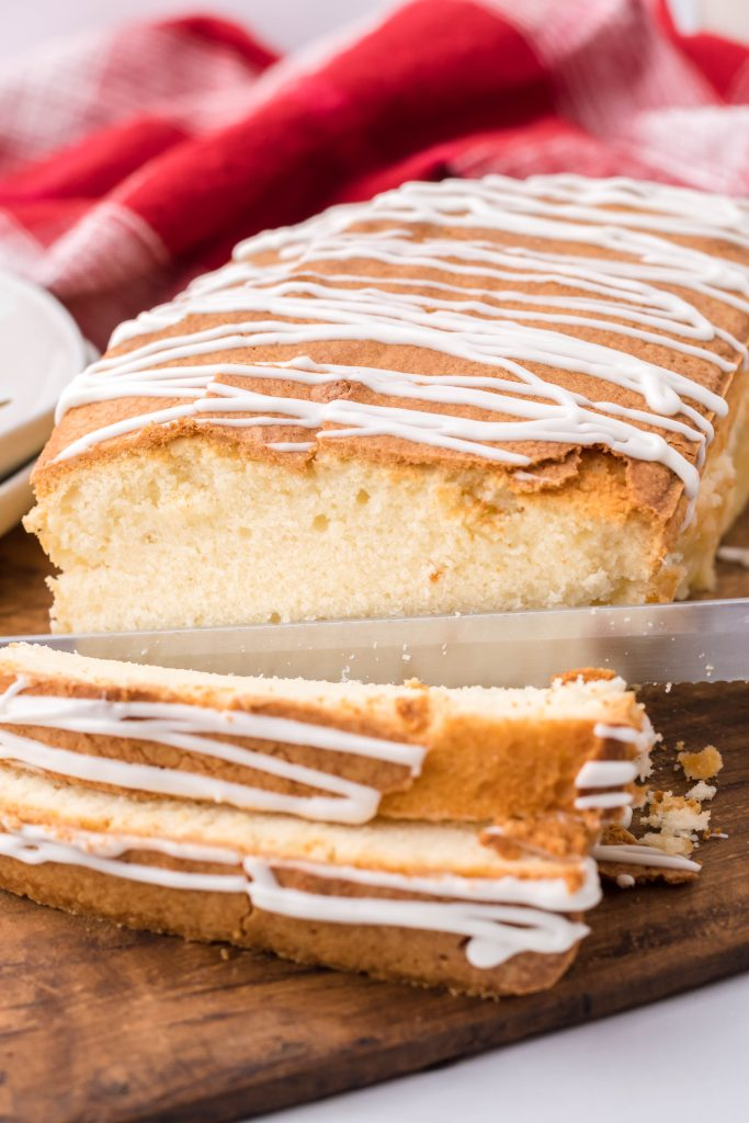 eggnog pound cake being shown sliced on a wooden cutting board