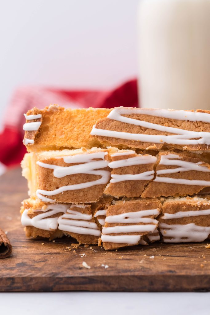 three slices off eggnog pound cake stacked on top of each other with a carafe of milk in the background