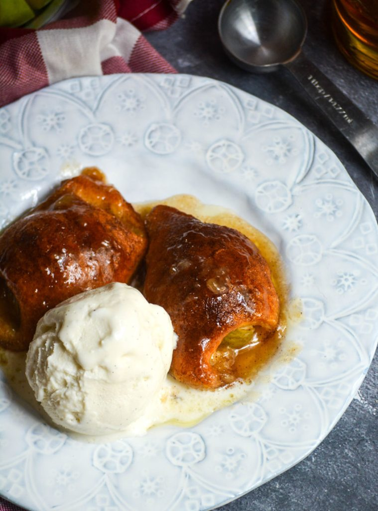 fireball whiskey glazed apple dumplings served on white plates with a scoop of vanilla ice cream