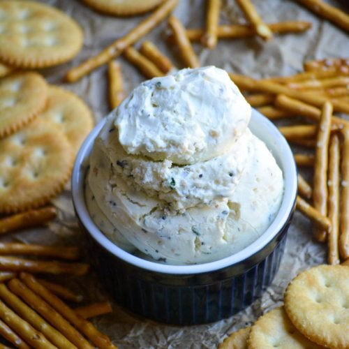 homemade boursin cheese served in a blue ramekin with crackers and pretzels on the side