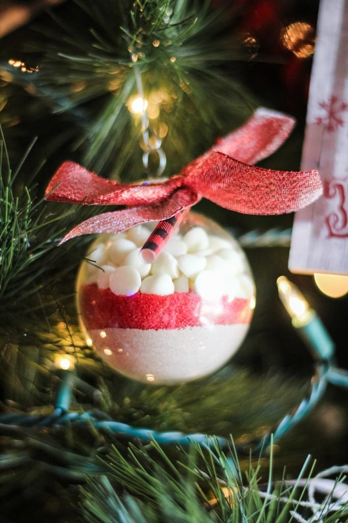 clear plastic ornaments filled with layers of hot cocoa mix, colored sprinkles, and mini marshmallows shown on a lit Christmas tree