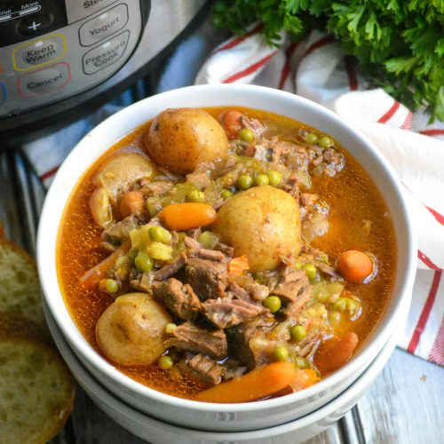 instant pot beef stew served in a white bowl with a pressure cooker shown in the background