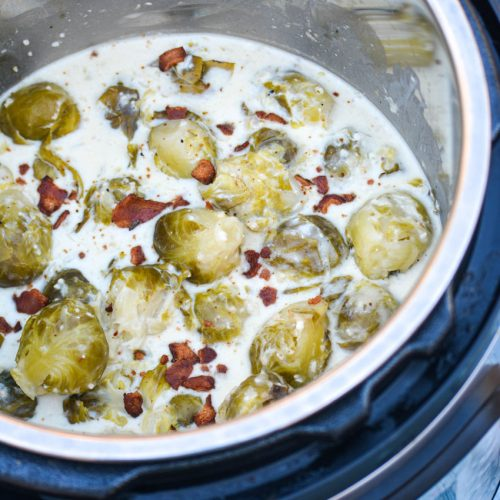 Instant Pot creamed brussels sprouts shown in the pot in a thick cream sauce and topped with crisp crumbled bacon