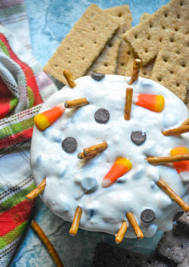 melted snowman dip shown in a black bowl surrounded by graham crackers for dipping