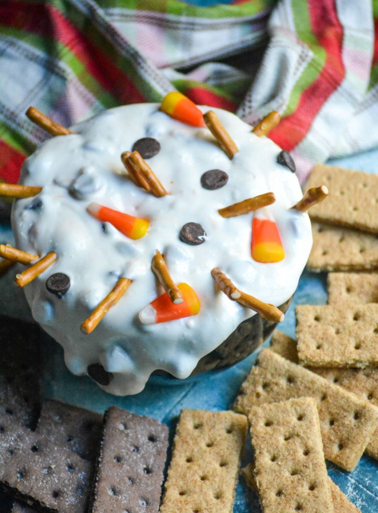 melting snowman dip shown in a black bowl surrounded by graham crackers for dipping