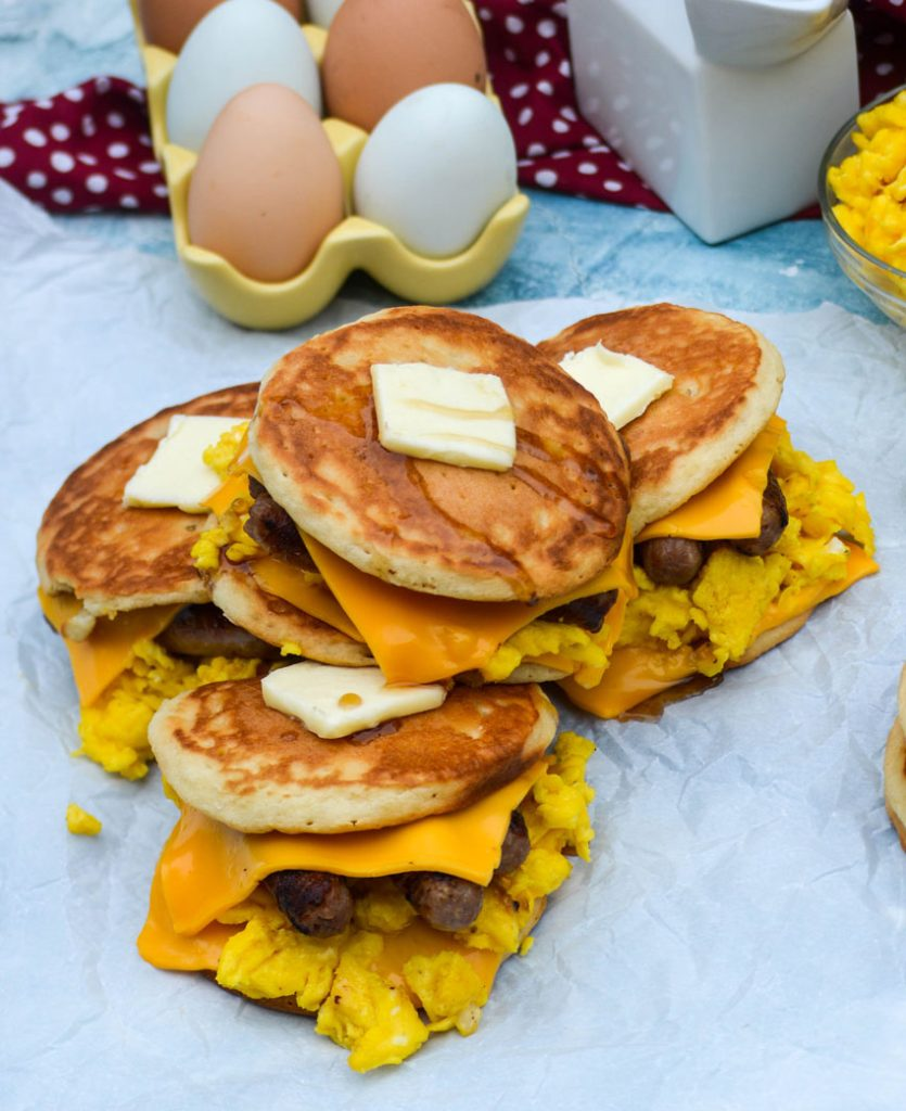pancake sandwiches piled together, shown topped with pats of butter