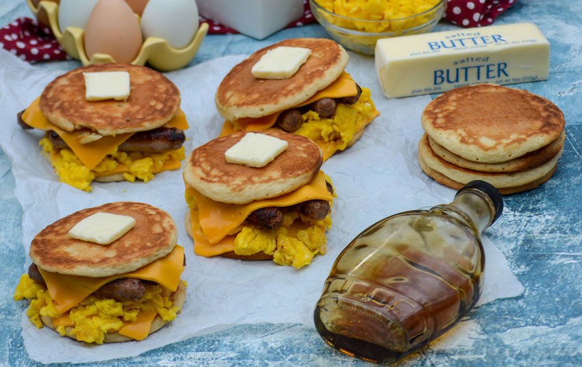 sausage egg and cheese pancake sandwiches shown topped with pats of butter