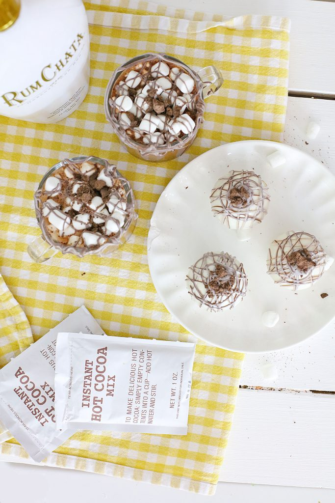 an overhead shot showing rumchata hot cocoa bombs on a white plate surrounded by mugs of cocoa and hot chocolate packets