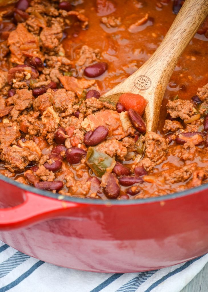 a wooden spoon dipping into a pot of cheeseburger chili