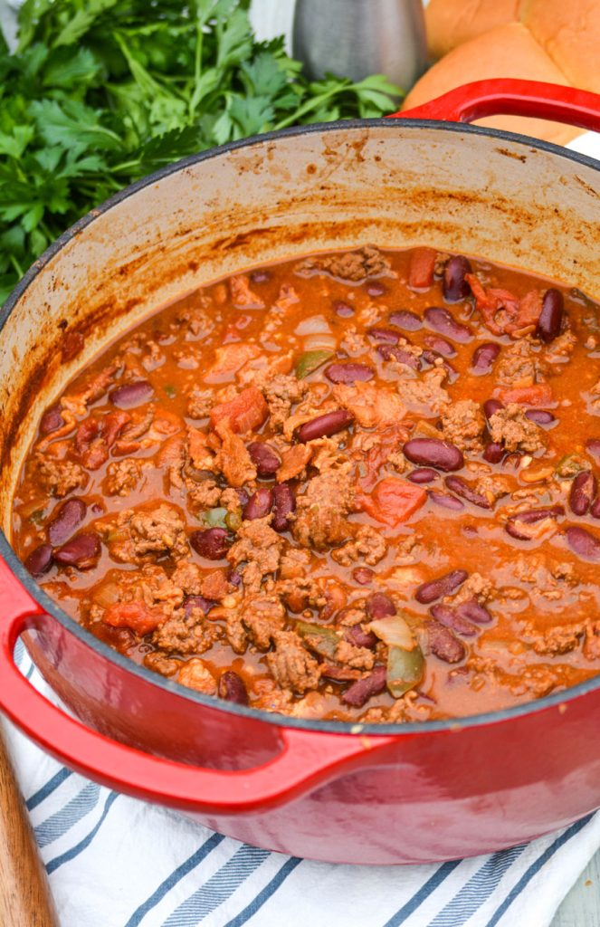 cheeseburger chili shown in a red dutch oven with a wooden spoon for serving