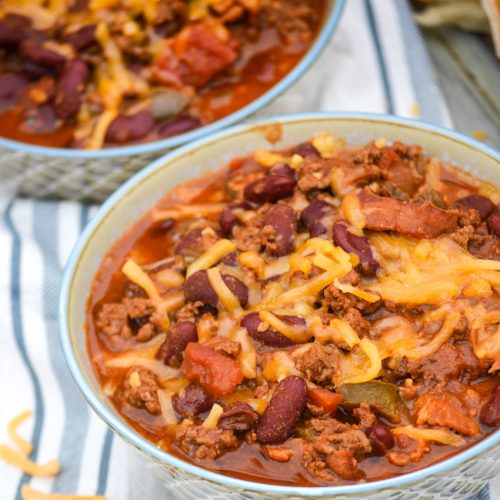 two bowls of cheeseburger chili topped with melted cheddar cheese