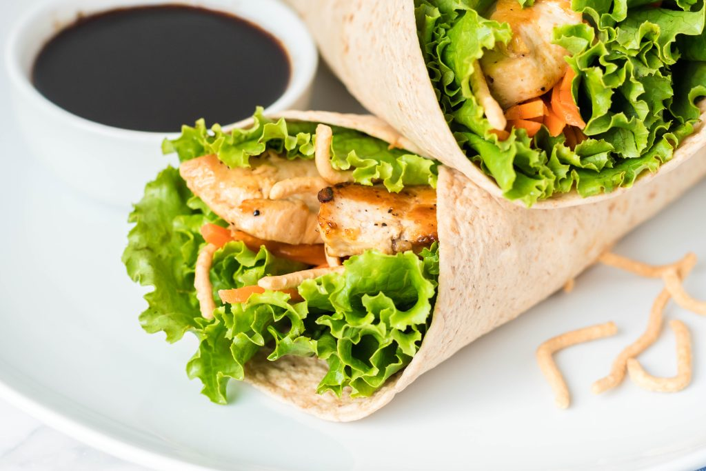 Asian chicken wraps served on a white plate with a dark sauce for dipping