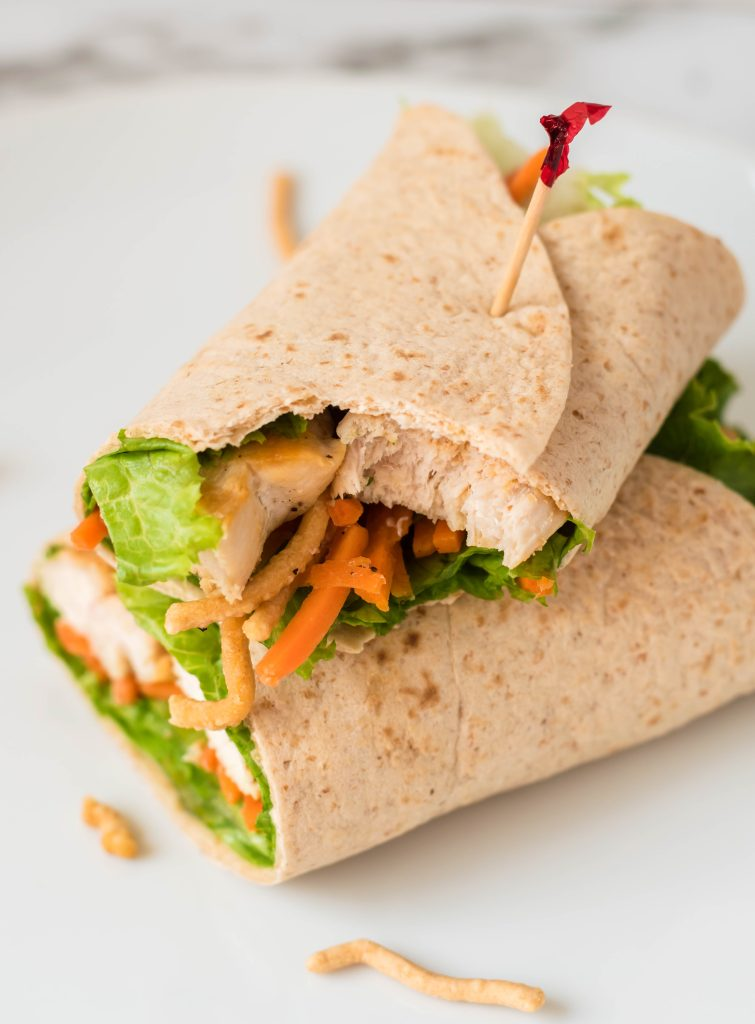 an Asian chicken wrap, cut in half and stacked together on a white plate, secured by tooth picks