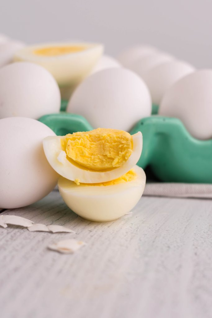 air fryer hard boiled eggs shown cooked and cut in half to reveal the solid yolk center on top of a bed of fresh eggs