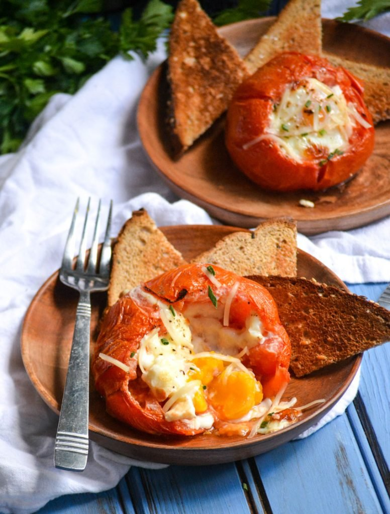 egg stuffed oven roasted tomatoes shown on wooden plates with toast triangles