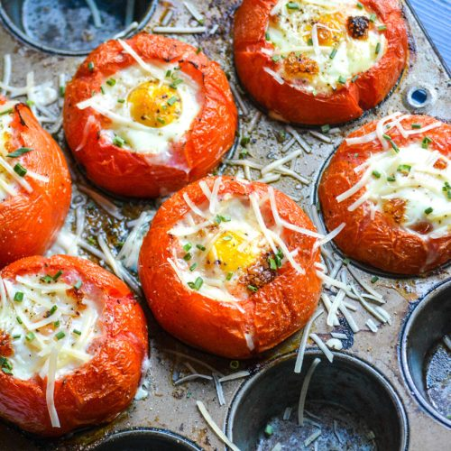 egg stuffed baked tomatoes shown in a muffin tin pan