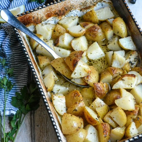 Greek lemon baked potatoes shown in a black & white casserole dish with a silver spoon for serving