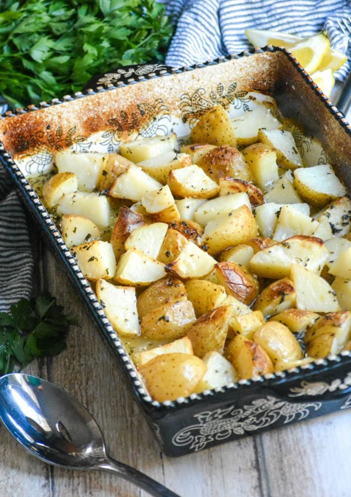 Greek Ellinikos Lemoni Patatas shown baked in a black & white casserole dish with lemon flavored broth