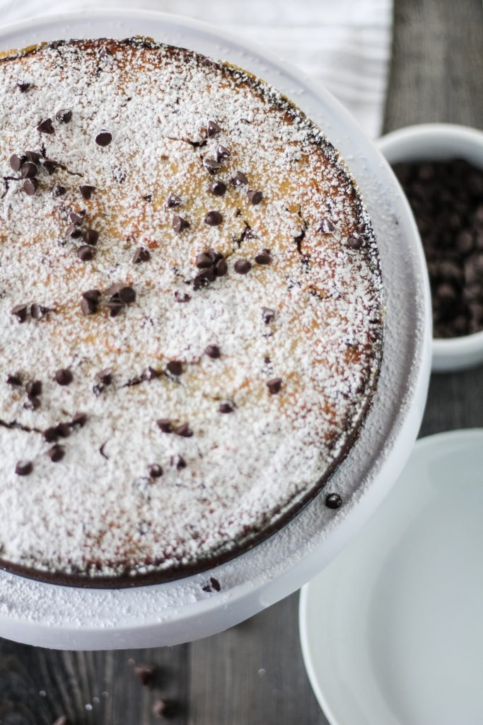 a powdered sugar sprinkled chocolate chip ricotta cake shown on a white cake plate