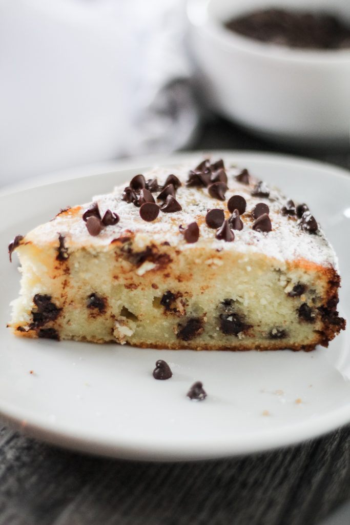 a slice of Italian ricotta cake shown on a white plate and sprinkled with miniature chocolate chips