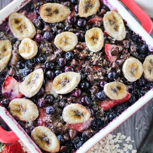 banana berry breakfast bake in a red square baking dish surrounded by fresh berries, oats, and a glass of milk