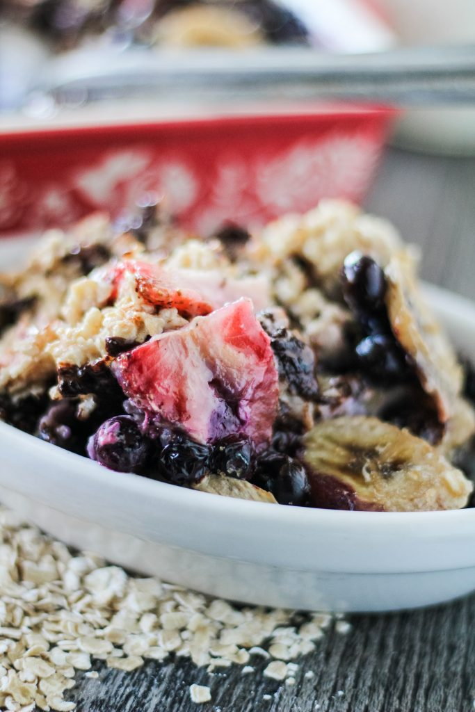 a serving of banana berry breakfast bake shown in a white oval bowl