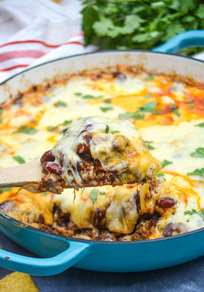 a wooden spoon shown lifting up a cheesy scoop of beef and bean nachos from a blue skillet