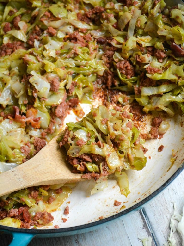 a wooden spoon shown with a scoop of corned beef & cabbage skillet