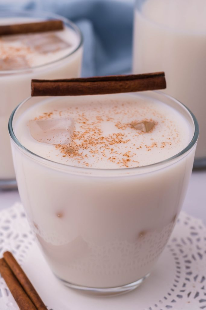 traditional horchata served in a clear glass with ice and topped with a pinch of ground cinnamon for garnish