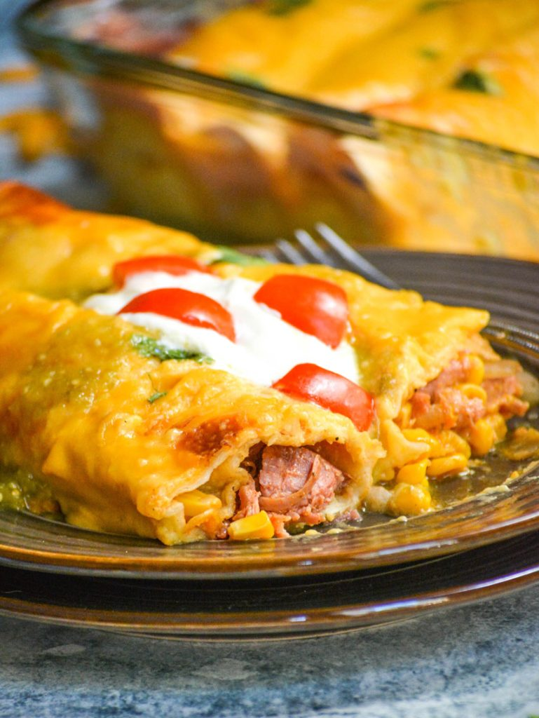 cheesy pulled pork enchiladas on a brown plate