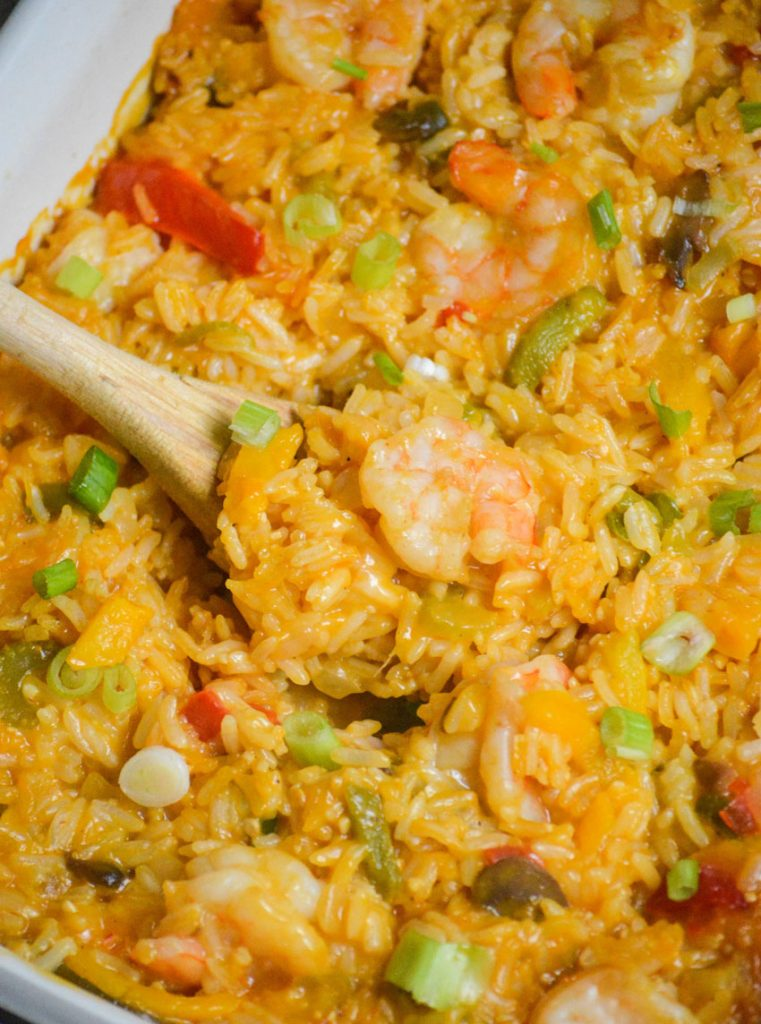 shrimp & rice casserole with a wooden spoon shown serving