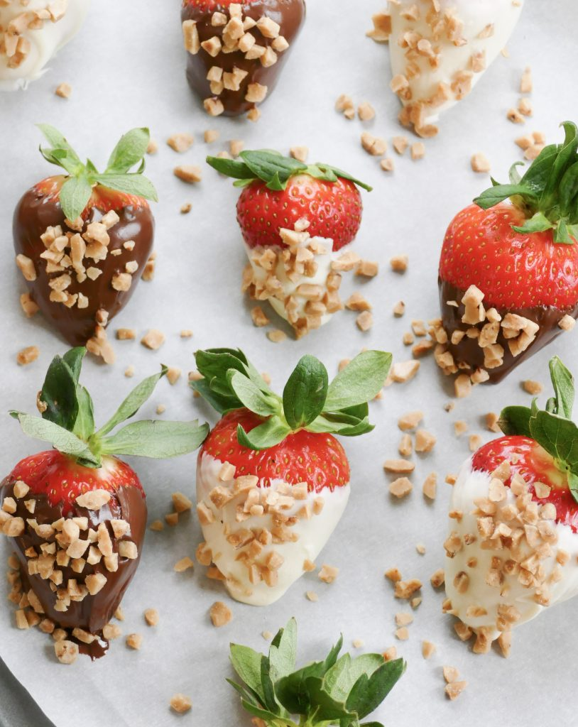 fresh toffee and chocolate covered strawberries arranged on a sheet of parchment paper