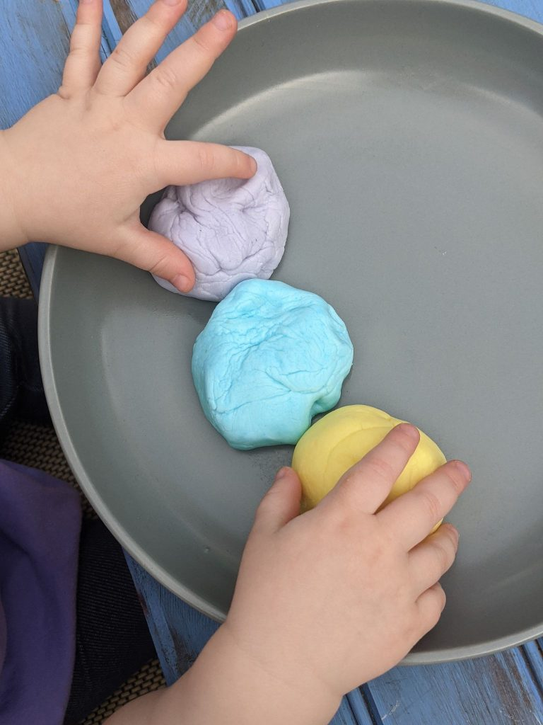 different colored balls of three ingredient edible peeps playdough on a gray plate with two little toddler hands