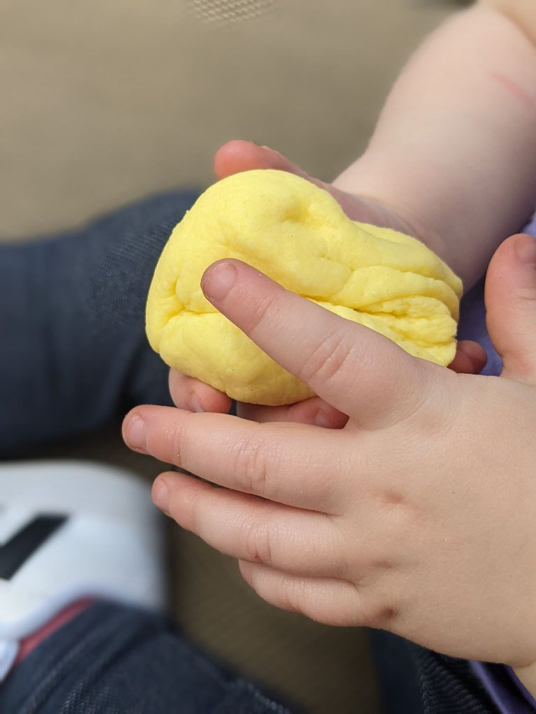 a yellow colored ball of peeps playdough shown in held in two little toddler hands