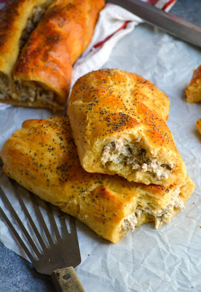 a classic sausage roll shown on a piece of parchment paper and broken open to reveal the creamy sausage filling inside