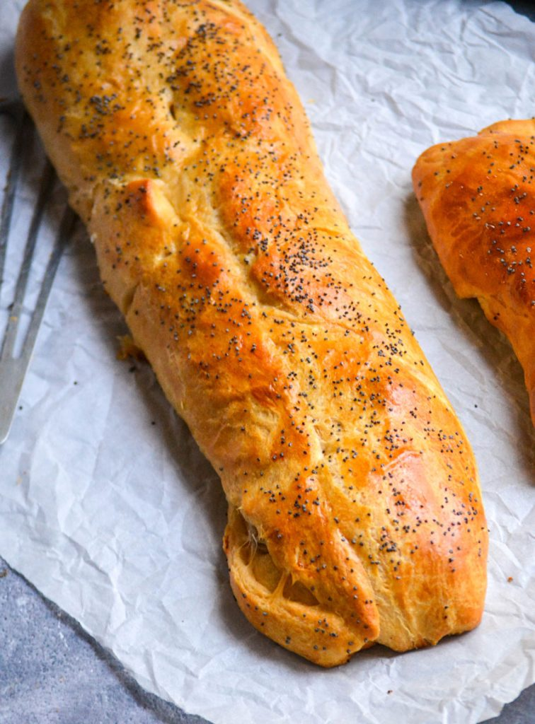 classic sausage roll recipe's golden brown log shown on a piece of wrinkled parchment paper