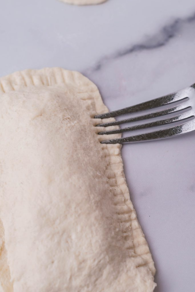 homemade hot pocket edges being crimped with a silver fork to seal so no filling leaks out during cooking