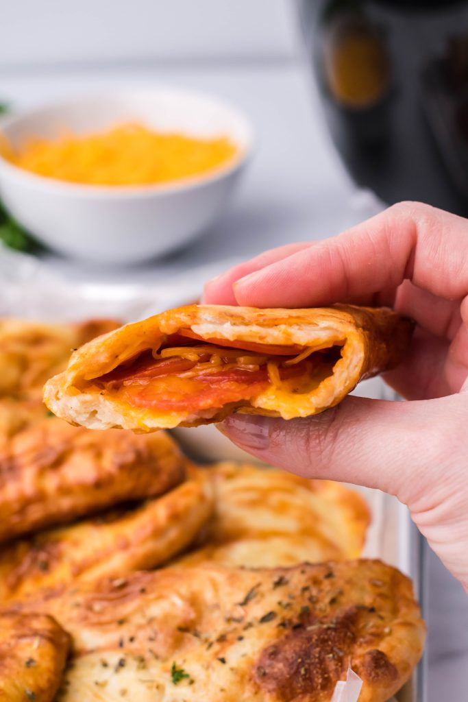 a hand holding up half a air fryer hot pocket to reveal the cheesy pepperoni filling inside